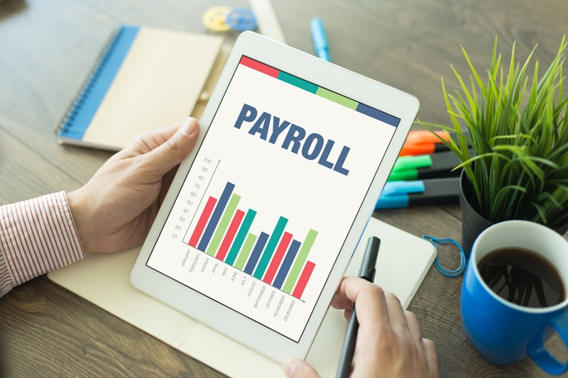 single touch payroll, image of someone holding ipad with payroll written on it